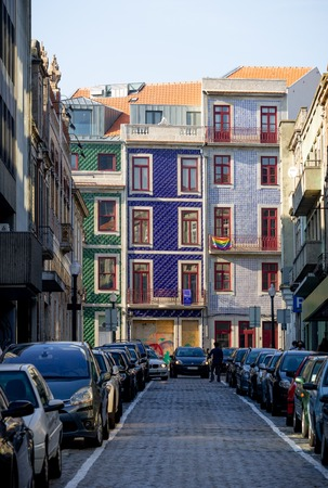 A car approaches in a Porto tight street with a tiled facade building in the background, while a man signals to advance. 新聞圖片