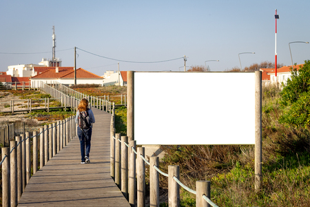 Young redheaded woman walks by an advertisement billboard mockup on a boardwalk amidst vegetation. Backpack. Rear view. Copy Space.