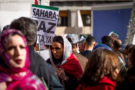 Madrid, Spain - November 17, 2018: Close-up of female protester holding a sign amidst other protesters at Plaza Maior, Madrid, supporting the decolonization and independence of Western Sahara from Spain. Editöryel