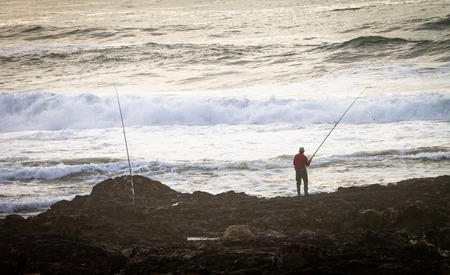 A fisherman and his fishing poles at the rocky shore, near the ocean. Waves, back view.