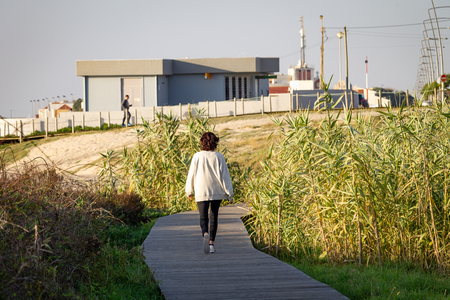 Middle-aged woman walks on boardwalk amidst vegetation. White Jacket. Rear view. Distant Buildings. Stock Photo