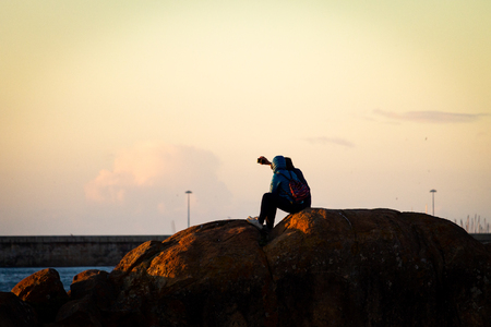 A couple takes a selfie while seated on some rocks at sunset. Warm light. Stock fotó