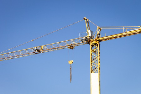 Yellow Crane on a clear blue sky background.
