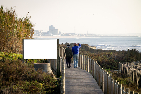 Two men, middle-aged and senior, walk by an advertisement billboard mockup on a boardwalk near the ocean. Rear view. Copy Space.