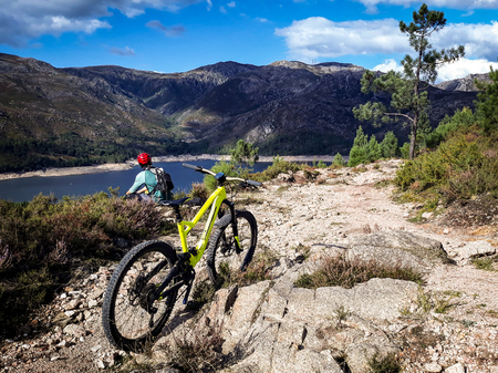 A mountain biker contemplates a lake in front of his yellow mountain bike. Banco de Imagens