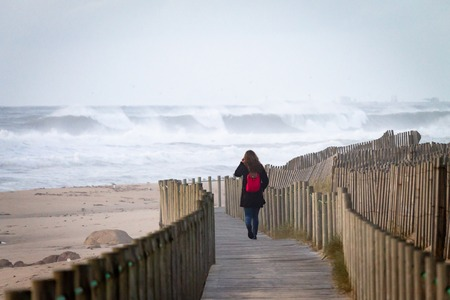 Woman walks on boardwalk near the beach. Waves crashing in the ocean. Back view. Red Backpack.