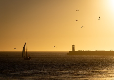 A sailboat approaches a silhouetted lighthouse at dusk with several people standing by and seagulls on the golden sky. Banco de Imagens
