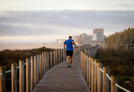 A man runs on a boardwalk near the beach. 30s. Blue Shirt. Back View. Cloudy day, warm light. Фото со стока