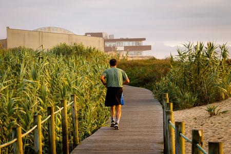 A man runs on a boardwalk between vegetation. 40s. Green Shirt. Back View. Cloudy day, warm light. 写真素材