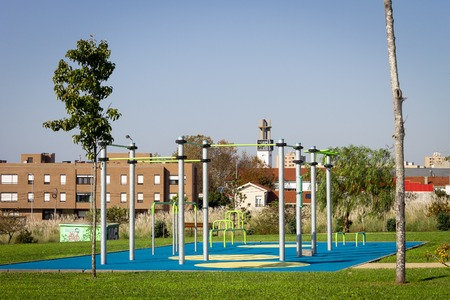 Empty outdoor gym workout space in a garden. Lifting Bars. Clear day.