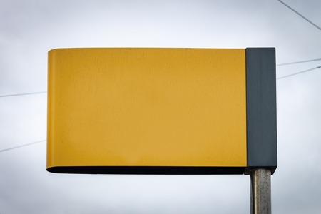 Dark Yellow Street Sign Advertisement Mockup. Copy Space. Iron Pole. Cloudy Background.