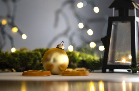 golden Christmas ball and other decoration and a lantern with Christmas String Light in a blurry background