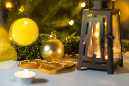 golden Christmas ball and a lantern with a candle inside surrounded with Christmas String Light in a blurry natural enviroment