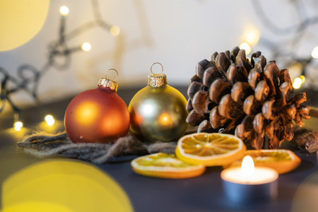 christmas decoration closeup of a pinecone with candels and a christmas ball, christmas string lights with blurry lightballs in the background, christmas feeling Фото со стока
