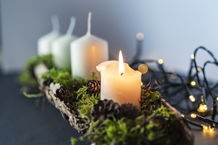 closeup of an advent christmas wreath line with 4 candels the first candel is burning, christmas light stripes in a blurred out background
