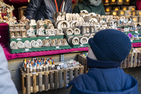 Young boy looking on Handmade Christmas decoration out of wood on a christmas market booth in meran south tyrol italy, small houses, wooden figures, candel cases Фото со стока