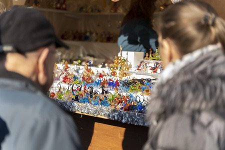 two people looking on beautiful handmade colorful glass figures on a christmas market booth in merano, south tyrol in italy during daylight Фото со стока