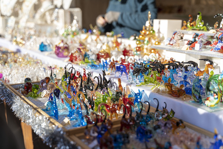 beautiful handmade colorful glass figures on a christmas market booth in merano, south tyrol in italy during daylight Фото со стока