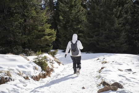 Women hiking with a backpackt hrough snow on a snowy hiking path in south tyrol italy