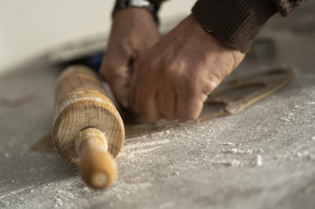 close up of a rolling pin and hands who are cutting out cookies of the biscuit dough in a kitchen