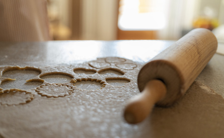close up of a rolling pin and a biscuit dough with cutted out cookies on a kitchen table Фото со стока