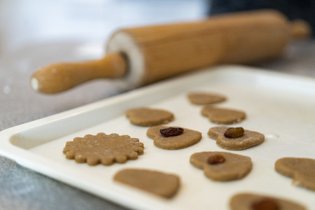 close up of a rolling pin and cutted out raw cookies in a baking plate