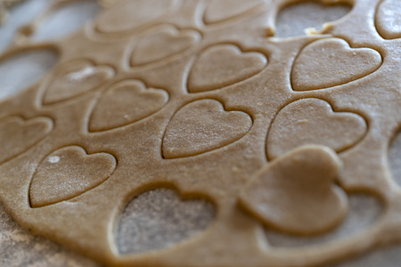 close up of biscuit dough with cutted out cookies in heart shape for valentines day Фото со стока