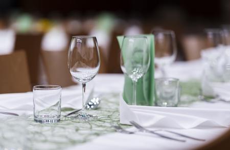 Nahaufnahme eines gedeckten Tisches auf einer Gala-Dinner-Party mit Weingläsern und verschwommenem Hintergrund