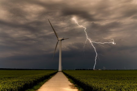 Powerful lightning strikes wind turbine in the afternoon photo