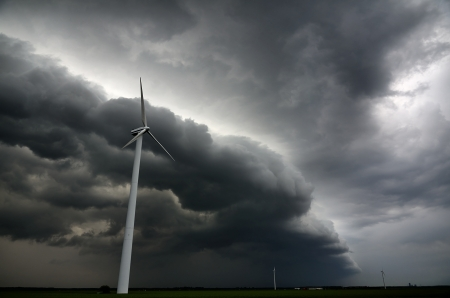 Dark shelfcloud preceding heavy thunderstorm at windturbine park photo