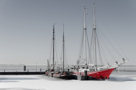 ice dam: Two sailing vessels locked into ice  in black and white with red  Stock Photo