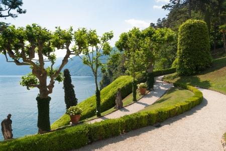 bellagio: Tranquil winding path in the Villa Balbianello garden along the shore of lake Como, Italy Stock Photo