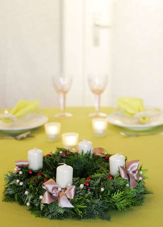 Christmas garland decorated with white candles, ribbons and red and white pearls on blurred green background with more candles, plates, and glasses. photo