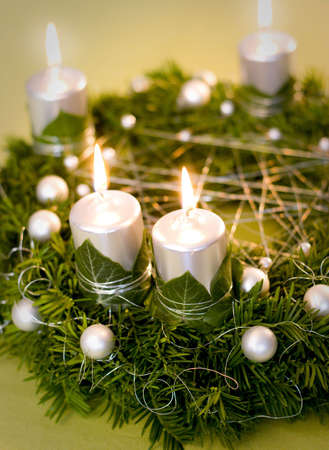 Christmas wreath with silver lighted candles, ivy leaves and white pearls nad balls on green and golden background. photo
