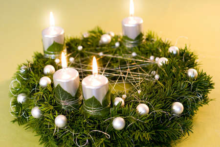 Christmas wreath with silver lighted candles, ivy leaves and white pearls nad balls on green and golden background. Stock Photo - 5915548