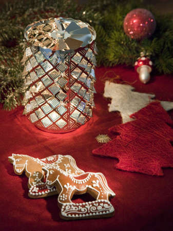 Gingerbread horses, rotating candleholder, little trees, and  other christmas decorations on a red tablecloth Stock Photo - 5915646