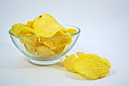 Crinkle cut potato chips in a bowl on a white background