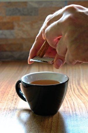 grating: Grating cinnamon into tea
