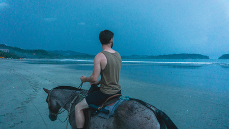 Man in tanktop riding a horse in the dusk at the beach