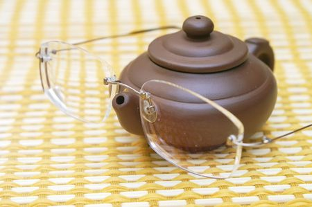 long sightedness: Glasses and teapot on authentic bamboo table-cloth Stock Photo