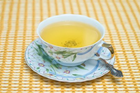 Cup of green tea on a table-cloth (focus on a cup) photo