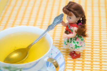 Small beautiful doll serving green tea