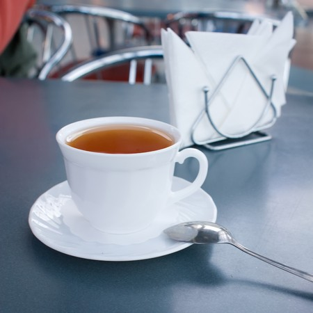 Cup of tea on a table (focus on a cup) photo