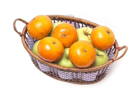 Tangerines and apples in a basket isolated on white background photo
