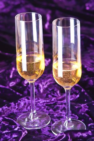 Two wineglasses with champagne on velvet photo