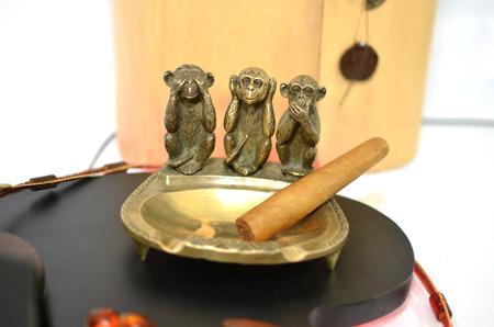 Copper ashtray with cigar and three monkeys photo