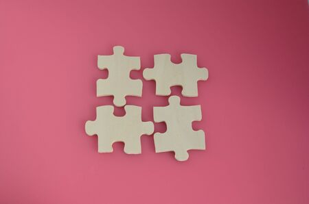 Four wooden puzzle pieces on a pink background Stock Photo