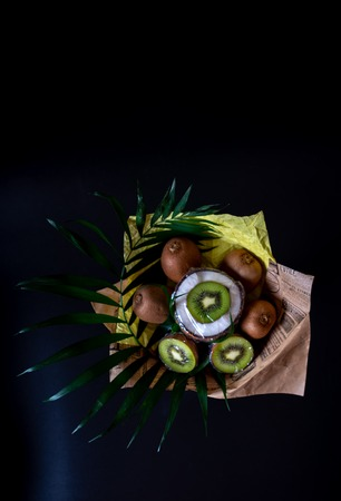Unique festive bouquet of coconut, kiwi and palm twigs on a black background. Vegetable bouquet. Fruits and Vegetables of the Healthy Concept.