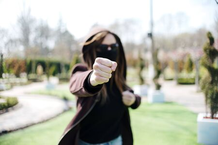 Young girl giving punch on unfocused background. Aggressive girl in a medical mask and glasses attacks.