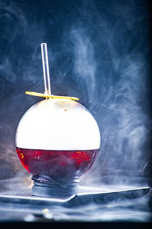 Spherical glass with smoke and alcohol. A cup of red cold cocktail with dry ice smoke and a caramelized lemon slices. Smoke on a black background.